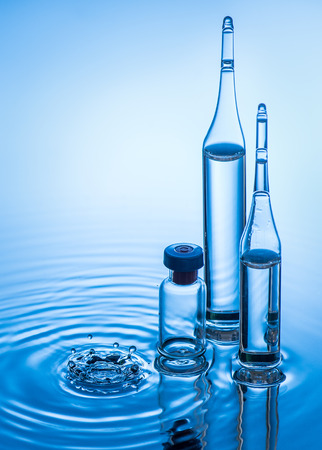 ampules: Medical ampules and botttle are standing in the blue water with water splash. Blue water background Stock Photo