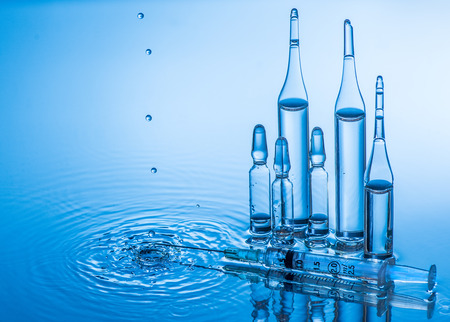ampules: Medical ampules and syringe are standing in the blue water with water splash. Blue background