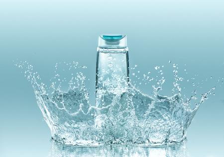 Moisturizing Shampoo für trockenes hair.The Flasche klare Flüssigkeit bleibt auf dem türkisfarbenen Wasser Hintergrund mit großen Spritzen Standard-Bild - 53629044