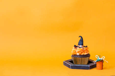 Halloween symbols, preparation for the holiday. Orange pumpkin cupcakes and wood decor. Bright background