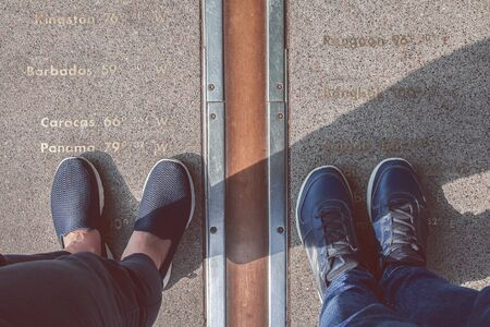 Two pairs of legs stand on either side of the Prime Meridian