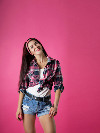 the girl cheerful in a shirt in a section on a pink background
