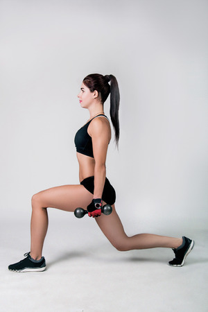 lunges: a girl in a sportwear does the fitness of exercise on a white background Stock Photo