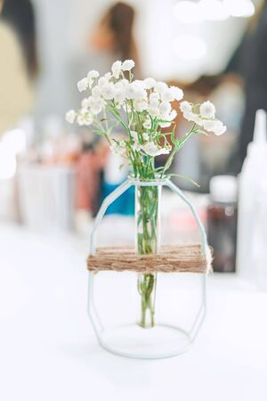 a small vase of flowers stands on a white table against a bright window
