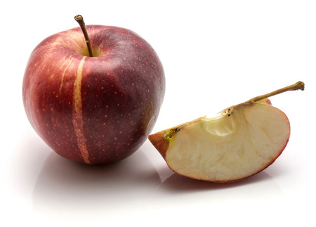 One whole Gala apple and a sliced quarter with a stem isolated on white background