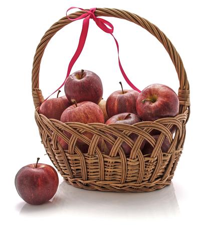 白い背景に隔離されたリボンを持つウィッカーバスケットのガラリンゴ 写真素材