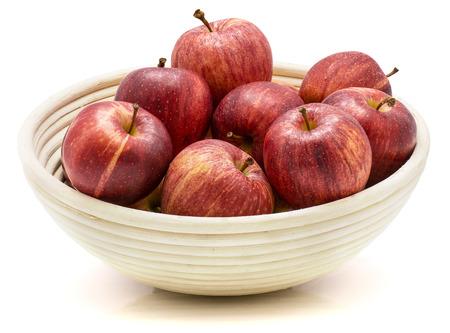 白い背景で隔離の籐ボウルにりんごをガラ