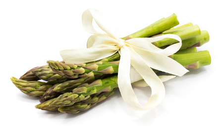 Bunch of raw asparagus tied with a creamy knot isolated on white background