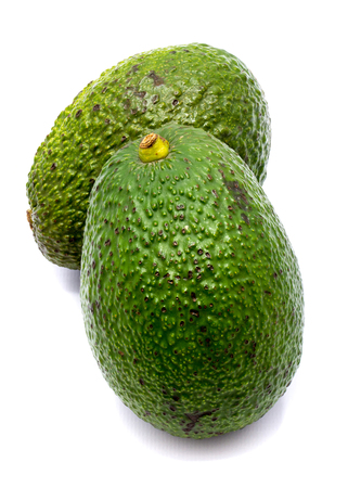 Two whole avocado (Persea americana, alligator pear) isolated on white background