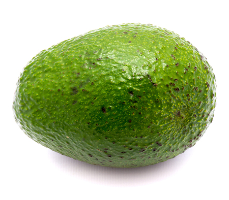 One whole avocado (Persea americana, alligator pear) isolated on white background
