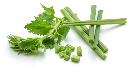 Sliced fresh celery pieces, sticks and leaves, isolated on white background