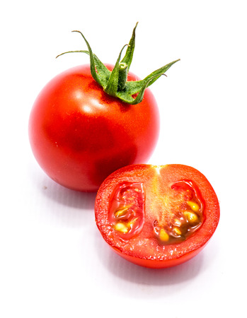 One whole red cherry tomato with green top and one half with seeds isolated on white background