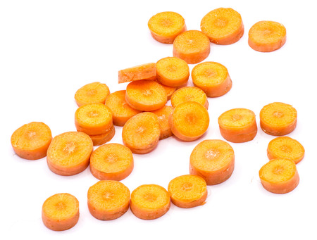Group of sliced round orange carrot circles in chaos isolated on white background