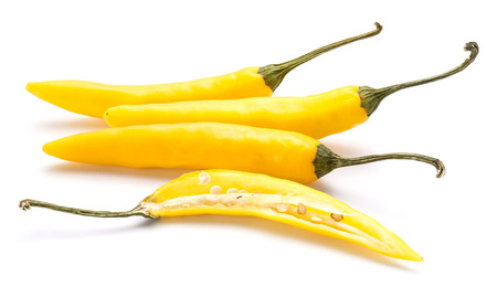 Yellow Chili peppers, three whole and one half isolated on white background