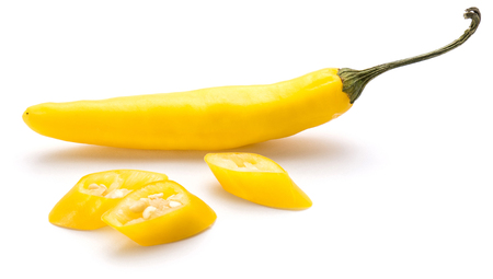 One whole yellow Chili pepper and three slices isolated on white background