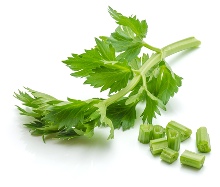 Sliced fresh celery pieces and leaves isolated on white background