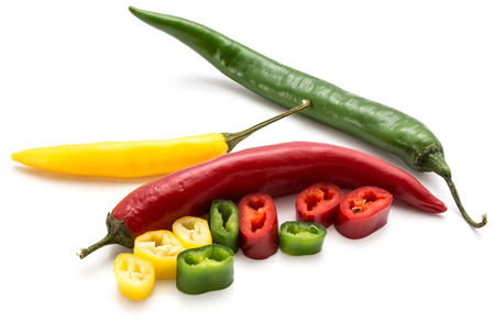 Whole Chilli peppers and slices isolated on white background three colors composition (red, yellow, green)