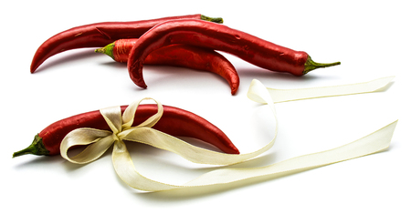 Group of four red Chilli, one is tied with a creamy bow, isolated on white background  Stock Photo