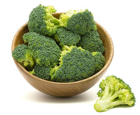 Verse broccoli in een houten kom die op witte achtergrond wordt geïsoleerd