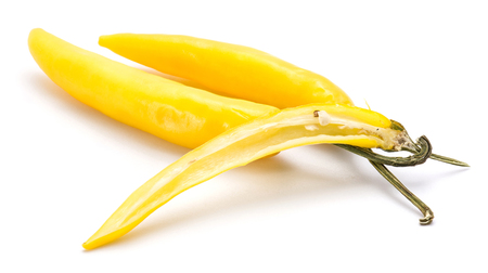 Two whole yellow Chili peppers, one half, isolated on white background