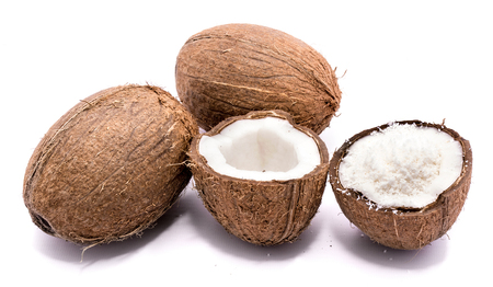 Two whole coconuts and two cracked coconut halves with shavings isolated on white background