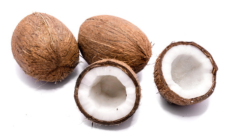 Two whole coconuts and two cracked coconut halves isolated on white background