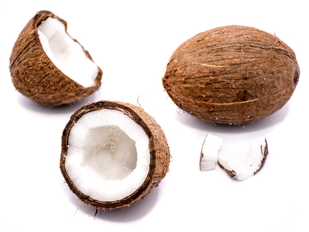 One whole coconut, two halves and meat pieces isolated on white background