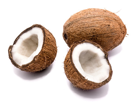One whole and two cracked coconut halves isolated on white background