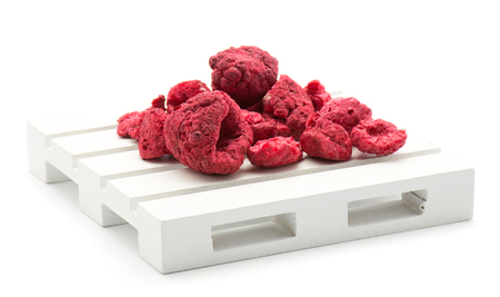 Freeze dried raspberries on a pallet isolated on white background