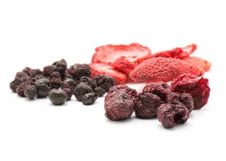 Freeze dried berries mix isolated on white background comparing strawberry cherry bilberry stacks