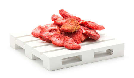 Freeze dried strawberries on a pallet isolated on white background