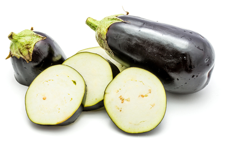 One whole and sliced eggplant (aubergine), cut in round circles, isolated on white background