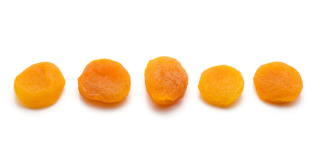 Five whole dried apricots in row isolated on white background