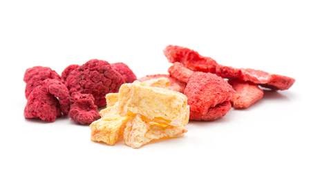 Freeze dried berries mix isolated on white background comparing strawberry raspberry pineapple stacks