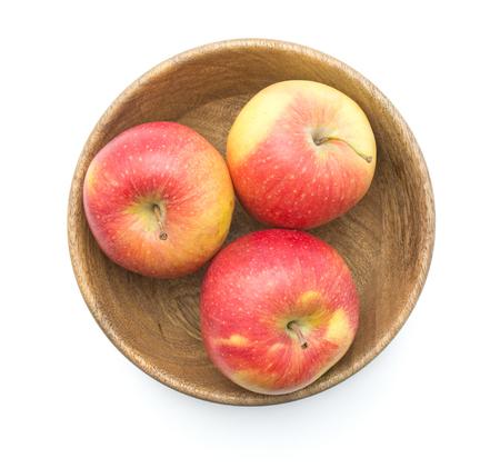 木製のボウルに 3 つのりんご (Evelina 品種) 平面図白地赤黄色の分離