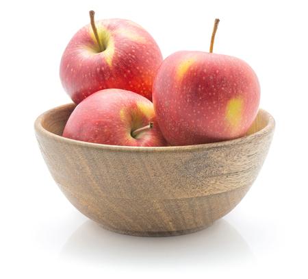 白い背景に隔離された木製のボウルに3つのリンゴ(エベリーナ品種)赤黄色