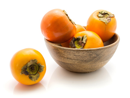 Persimmon Kaki in a wooden bowl isolated on white background