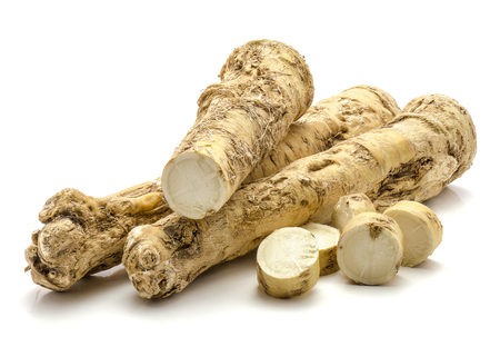 Two whole one half and sliced circles of fresh horseradish root isolated on white background