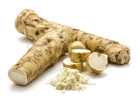 One whole, one half and freshly grated mash of horseradish root, isolated on white background, sliced circles