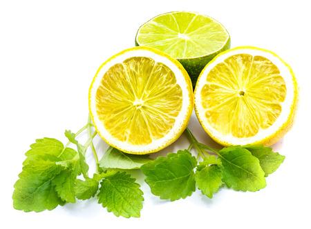 Two cross section lemon halves, one lime half and fresh green lemon balm leaves isolated on white background