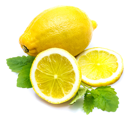 One whole yellow lemon with a half and slice and fresh green lemon balm leaves isolated on white background