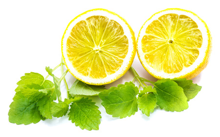 Two cross section lemon halves and fresh green lemon balm leaves isolated on white background   Stock Photo