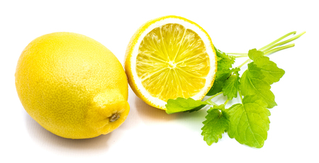 One whole yellow  cross section half and fresh green lemon balm leaves isolated on white background   Stock Photo