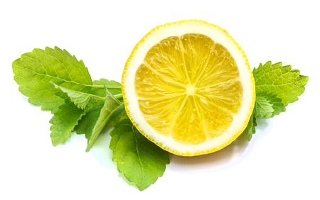 One cross section lemon half and fresh green lemon balm leaves isolated on white background