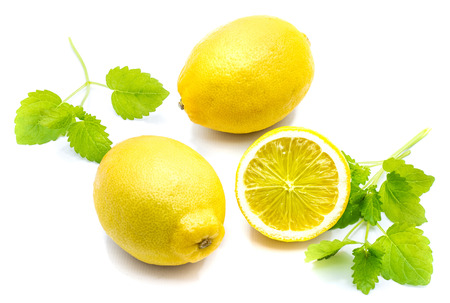 Pair of whole yellow lemons, cross section half and fresh green lemon balm leaves isolated on white background
