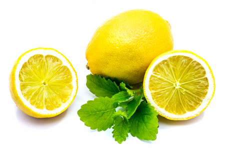 One whole single yellow  two cross section halves and fresh green lemon balm leaves isolated on white background