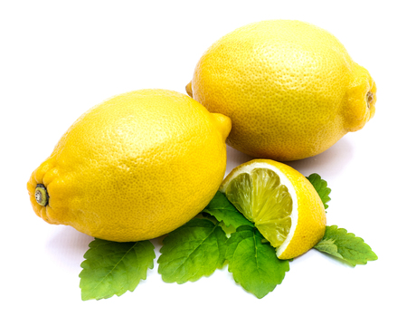 Two whole yellow lemons and slice with fresh lemon balm leaves isolated on white background