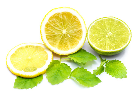 Lemon half and slices with fresh lemon balm leaves isolated on white background  Stock Photo