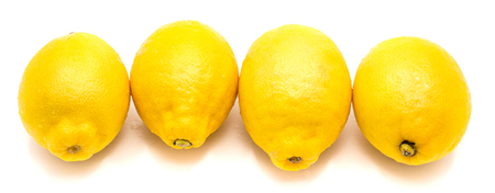 Group of four whole yellow lemons in row isolated on white background