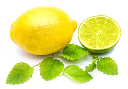 One whole lemon, lime half with fresh lemon balm leaves isolated on white background  Stock Photo